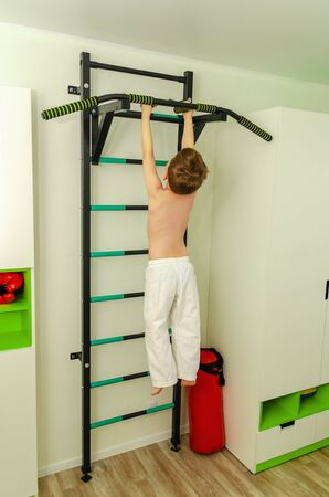 Little boy of preschool age does morning exercises on a home horizontal bar