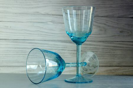 Two old glasses of blue glass on a wooden background, close up