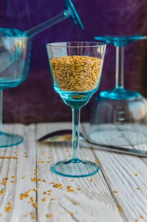 Flax seeds on the background of old cutlery and glass goblets. Close-up Archivio Fotografico