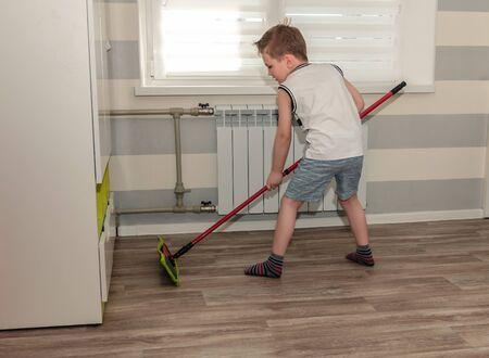 Little boy cleans his room, mops floors