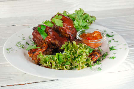Grilled fried meat on a plate with salad and herbs, shish kebab in tomato sauce Archivio Fotografico