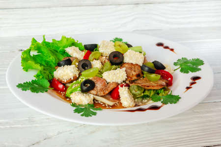 summer vegetable salad on a white dish on a wooden background