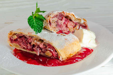 Hot fruit strudel with apples and cherries in cranberry sauce with spices and a slice of butter