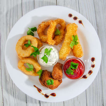 Deep-fried breaded onion rings on a plate with herbs Archivio Fotografico