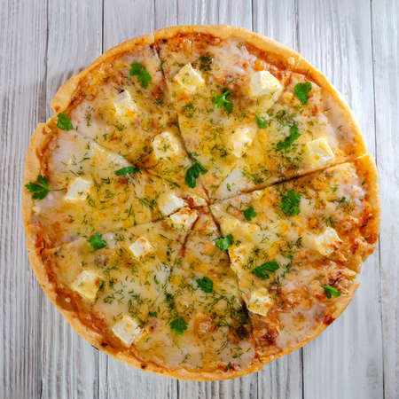 pizza with cheese vegetables and meat on a wooden background