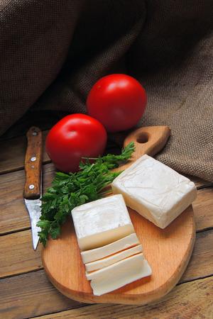 Groot gedeelte van gekruide halloumi of feta kaas grillen in aluminiumfolie over hete kolen in een barbecue buiten op groen gras Stockfoto