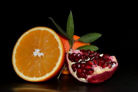 pomegranate fruit and orange on black background