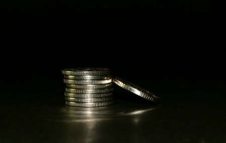 silver coin stack isolated on black background. Space for text