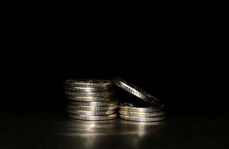 silver coin stack isolated on black background with reflection. Space for text