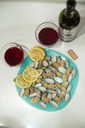 Delicious clam Spisula on foil cooking in the oven grilled next to glasses and a bottle of red pomegranate wine