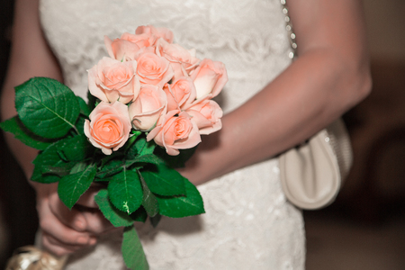 The girl, the bride is holding a beautiful colorful blooming bouquet of roses.