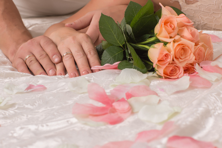 Hands bride and groom holding a beautiful colorful blooming bouquet of roses, lie on the bed