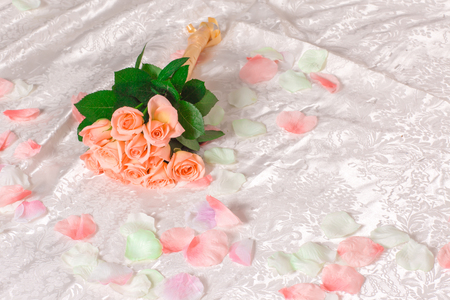 Very beautiful soft delicate pink roses with petals lie on the bed, romantic bouquet of pink roses on white sheets, romantic concept