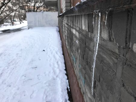 Icicles hang on the visor of a gray building next to the road, spring thaw. Archivio Fotografico