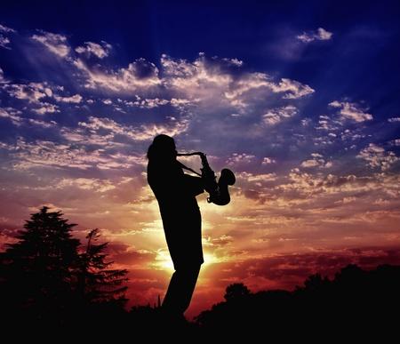 saxof�n: El saxofonista juega un saxof�n. Armon�a de sonidos de un saxof�n y la belleza de la puesta de sol de la naturaleza Foto de archivo