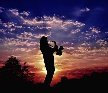 saxophone: The saxophonist plays a saxophone. Harmony of sounds of a saxophone and beauty of the nature sunset Stock Photo