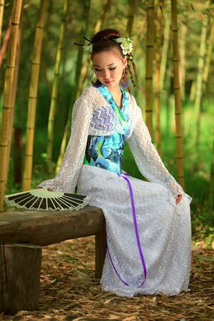 The Japanese with a fan, sitting on a bench in bamboo wood photo
