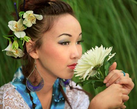Japanese girl holds flower, against green grass photo