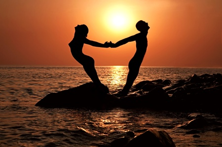 Love pair keeps for hands, standing a back to each other, between them the sun, the sea, a decline shines Standard-Bild