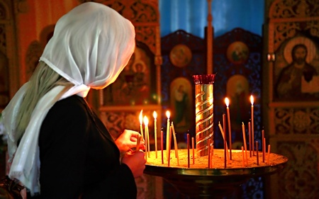 The girl prays in church about candles and icons photo