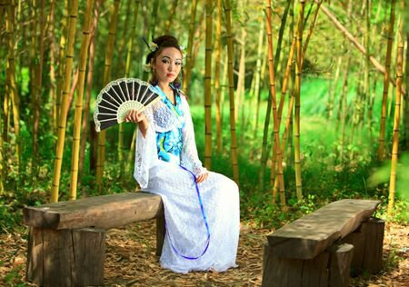 The young girl - the Japanese dressed in a kimono, is on the nature photo