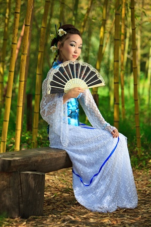 The young girl - the Japanese dressed in a kimono, is on the nature Stock Photo - 9416517