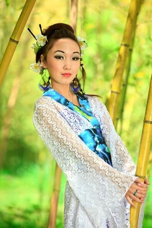 Das junge Mädchen - die Japaner in einen Kimono gekleidet ist auf die Natur