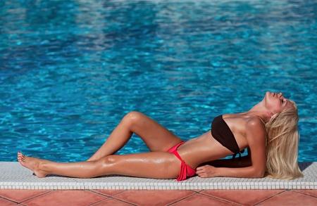 Die schönen Mädchen sonnt sich am Pool Standard-Bild
