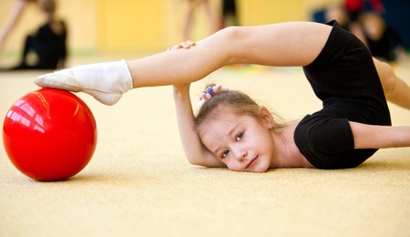 young gymnast doing exercise with ball