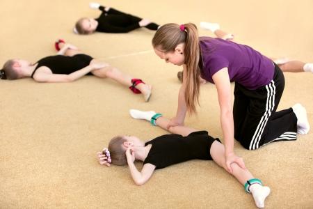 acrobacia: La joven gimnasta con el entrenador Foto de archivo