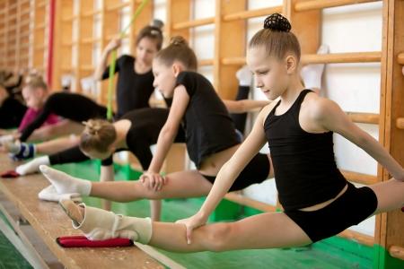 gymnastik: Unga flicka gymnaster i träning - stretching