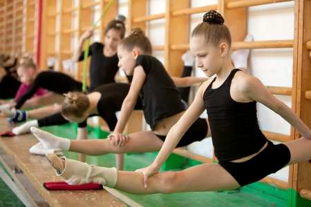 gymnastics sports: Young girl gymnasts in training - stretching Stock Photo