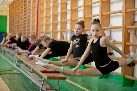 balance beam: Young girl gymnasts in training - stretching Stock Photo