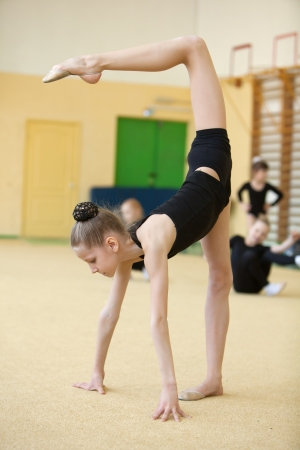 balance beam: young gymnast stretching and training