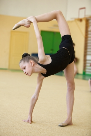 female gymnast: young gymnast stretching and training