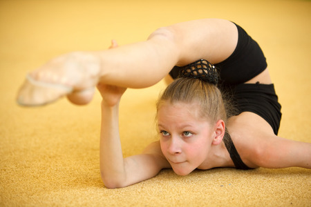 acrobat gymnast: Childrens in sports-young gymnast train your body
