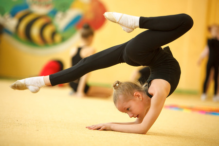 female gymnast: Childrens in sports-young gymnast train your body