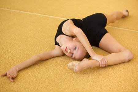 acrobacia: Niños en gimnasta deportivo jóvenes entrenan su cuerpo
