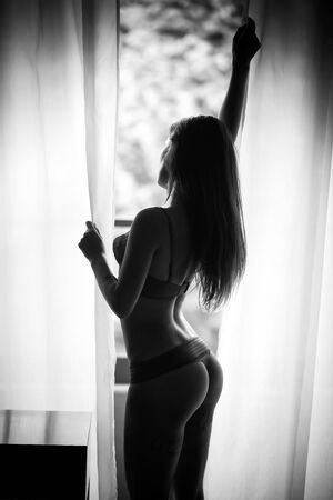 Sexy Silhouette eines Mädchens am Fenster, schwarz und weiß Standard-Bild