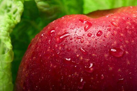 Roter Apfel in Blättern von Chinakohl