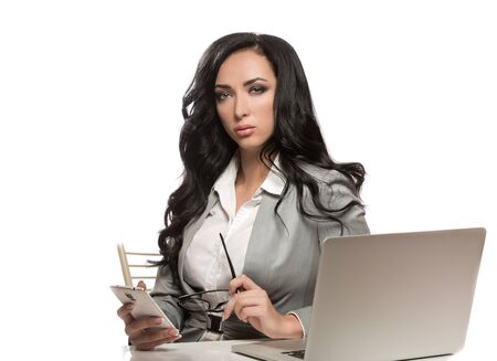 Girl is sitting at the laptop dressed in business style with glasses and phone