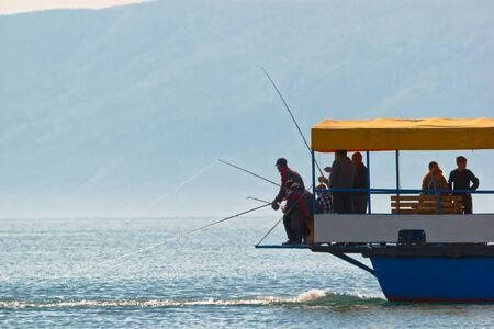 approaches: Fishing from the standing ship on island Olkhon on lake Baikal. The ship working screw creates flow on which the fish approaches