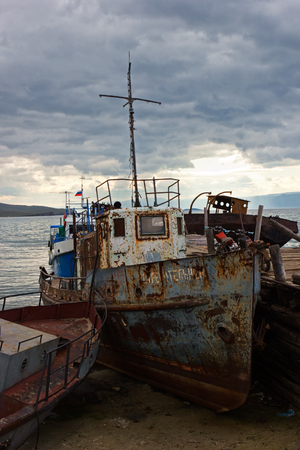 inshore: The old ship is moored inshore lakes Baikal about settlement Huzhir on island Olkhon