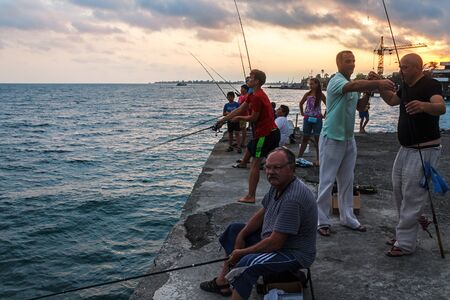 People fish in Black sea from landing stage