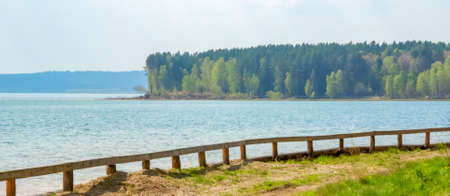 Walking path with a wooden fence along the shore of a large blue lake on a background of trees in summer, 写真素材