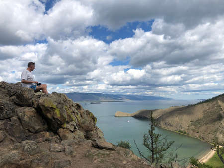 Man sits on a mountain top. Success concept