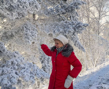Smiling woman enjoying winter sunny day in snowy forest.