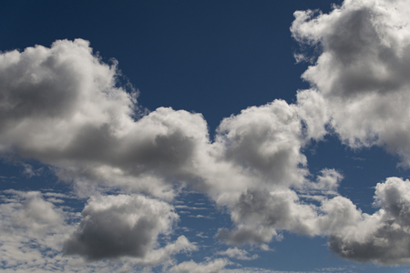 White and fluffy summer clouds against the clear sky. Stock Photo
