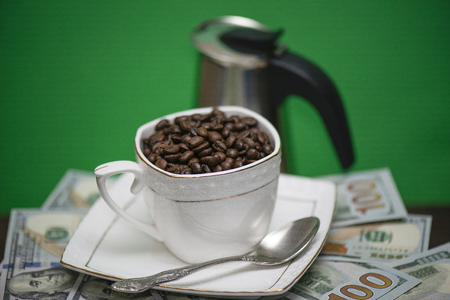 Cup with roasted aromatic beans on a green background and blurred the coffee maker Banco de Imagens