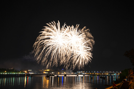 Fireworks in the form of a glowing ball with similar branches of cranberry fireworks to the day of the city in Kostroma